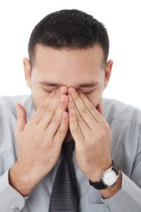 young businessman covering his eyes as if crying,thinking or under extreme stress