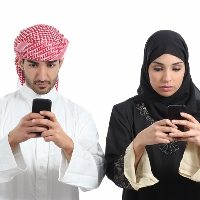 Front view of a saudi couple addicted to the smart phone isolated on a white background