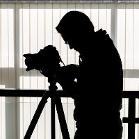 Silhouette of photographer and cameraman shot the video on a tripod at the workplace indoors