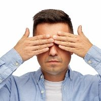 face of man covering his eyes with hands